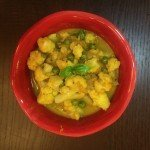 photo of cauliflower and green pea curry in red bowl