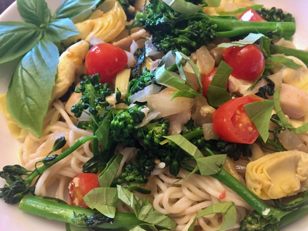 closeup photo of Mediterranean Pasta with broccolini, artichokes, and fresh basil