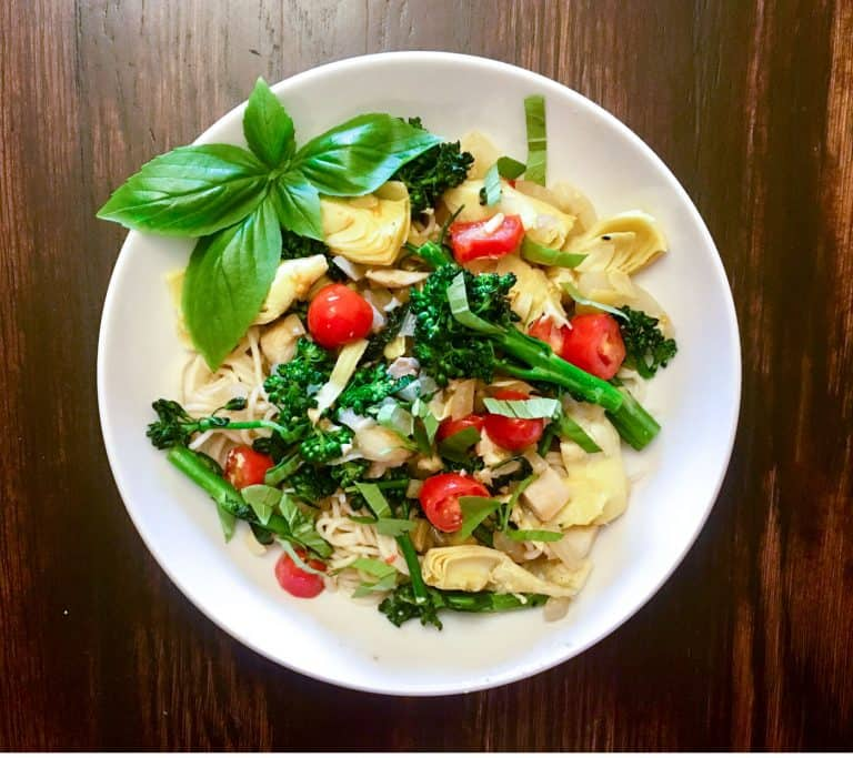photo of Mediterranean pasta with broccolini, artichokes, and fresh basil on white plate